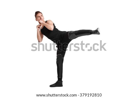 attractive young man kicking foot forward, on a white background
