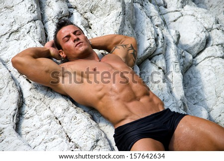 Attractive young man  laying naked on white rocks, eyes closed, wearing only black swimming suit - stock photo