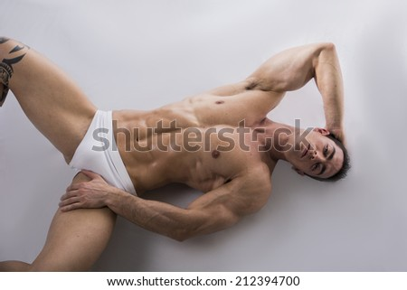 Attractive young man laying on the floor with naked muscular ripped body, hand under head - stock photo