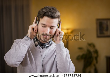 Attractive young man listening to music on headphones, eyes closed. Indoor shot in house - stock photo