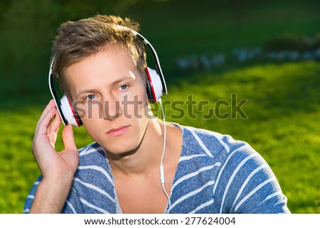 Attractive young man listening to music. Outdoor. Spring - stock photo