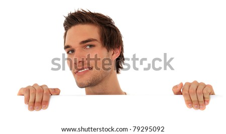 Attractive young man looking from behind a white wall. All on white background. - stock photo