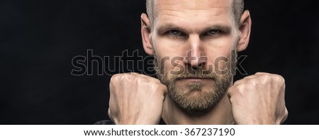 Attractive young man on a dark background holding his fists at his face.