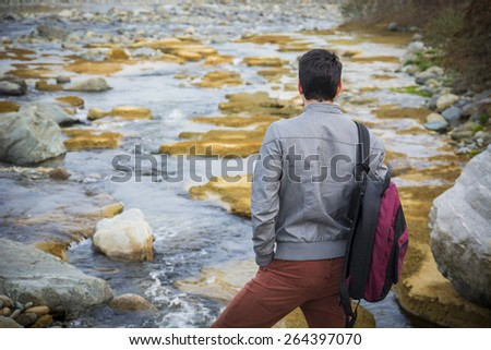 Attractive young man outdoor in nature, at river or water stream, seen from the back, with backpack or rucksack