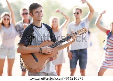 Attractive young man plays guitar against dancing friends, outdoors - stock photo