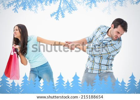 Attractive young man pulling his shopaholic girlfriend against frost and fir trees in blue - stock photo