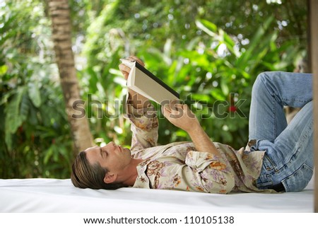 Attractive young man reading a book and laying down on an outdoors bed in a tropical lush garden while on holiday. - stock photo