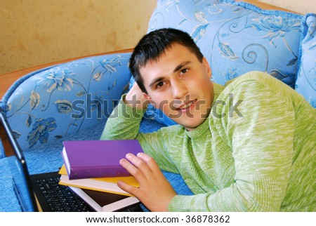 Attractive young man reading a book in bed.