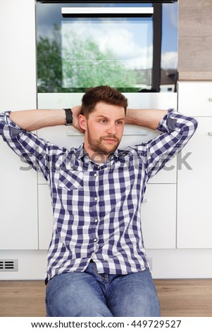 Attractive young man resting in a modern kitchen. Young man sitting leaning against the kitchen waiting for his girlfriend.