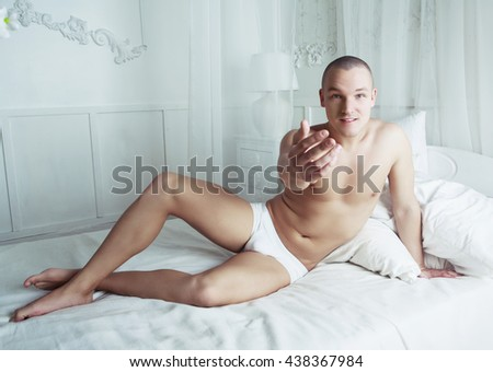 attractive young man resting in bed at home  - stock photo