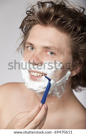 Attractive young man shaving with razor and smiling. High resolution image. See more in my portfolio
