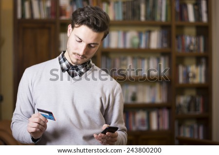 Attractive young man shopping online on mobile phone, holding credit card - stock photo