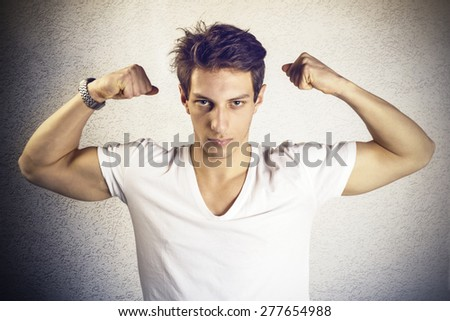 Attractive young man showing biceps - stock photo