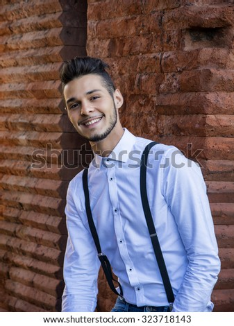 Attractive young man sitting against brick wall, looking at camera smiling. Three quarters shot