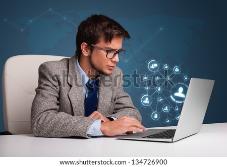 Attractive young man sitting at desk and typing on laptop with social network icons comming out