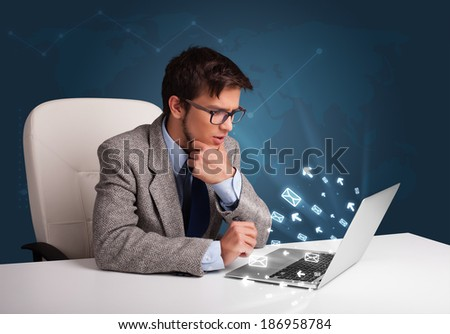 Attractive young man sitting at dest and typing on laptop with message icons comming out - stock photo