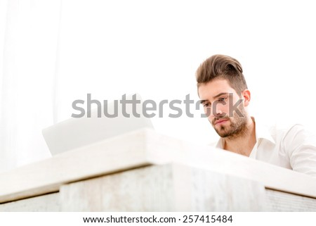 Attractive young man sitting at the table with a laptop computer.  - stock photo