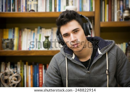 Attractive young man sitting listening to music on a set of stereo headphones in his study at home in front of a bookcase filled with books - stock photo