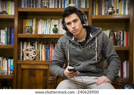 Attractive young man sitting listening to music on a set of stereo headphones in his study in front of a bookcase filled with books - stock photo
