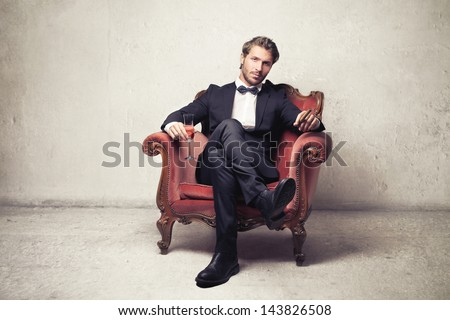 attractive young man sitting on an armchair - stock photo