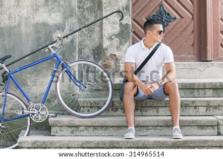 Attractive young man sitting on the steps of the building in the old town with his bicycle beside him - stock photo