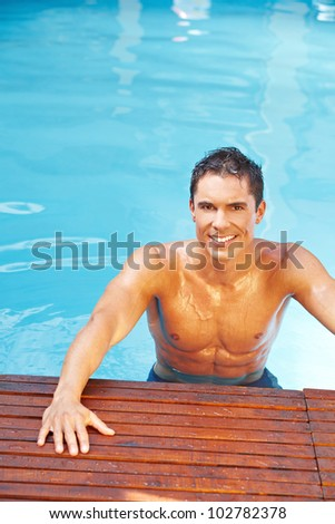 Attractive young man smiling in swimming pool with blue water - stock photo