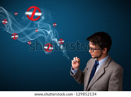 Attractive young man smoking dangerous cigarette with no smoking signs - stock photo