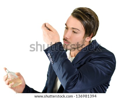 Attractive young man spraying and smelling fragrance or cologne, isolated - stock photo