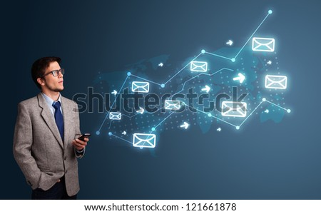 Attractive young man standing and holding a phone with arrows and message icons - stock photo