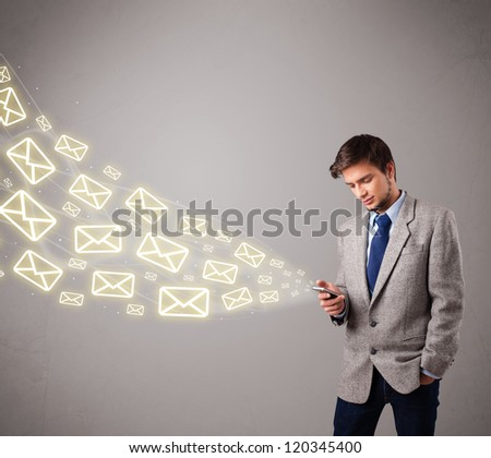 attractive young man standing and holding a phone with message icons - stock photo