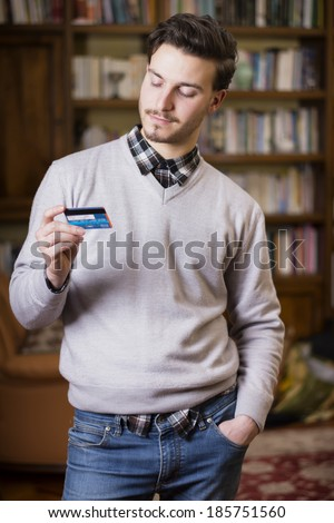 Attractive young man standing at home holding credit card, looking at it - stock photo