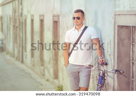 Attractive young man standing on the street with his bicycle beside him - stock photo