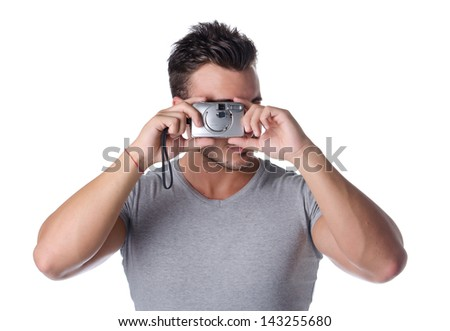 Attractive young man taking picture with compact photo camera - stock photo