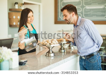 Attractive young man trying to decide what to buy while employee shows him their products in a cake shop