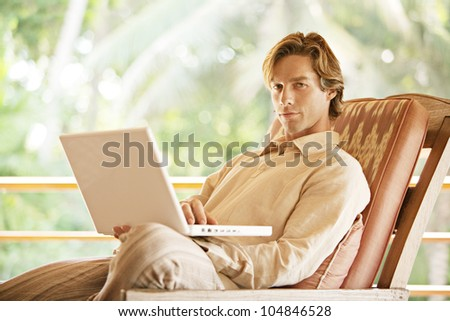 Attractive young man using a laptop computer while sitting on a tropical garden's balcony.