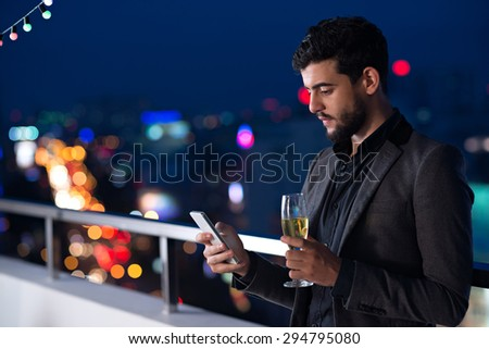 Attractive young man using application on his smartphone and drinking champagne - stock photo