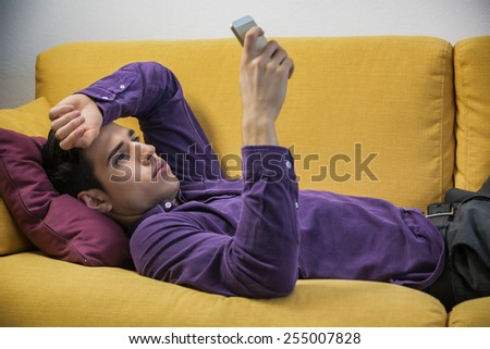 Attractive young man using cell phone while laying on couch, with serious expression - stock photo