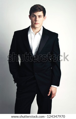 Attractive Young Man wearing a tuxedo, casually unbuttoned. - stock photo
