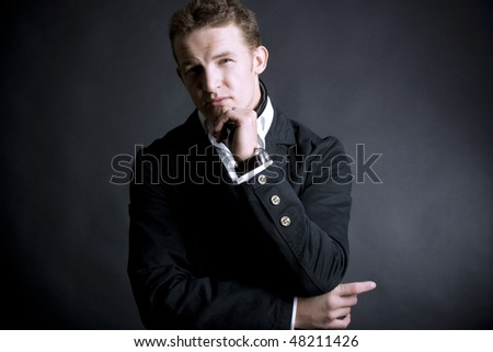 attractive young man wearing elegant black suit - stock photo
