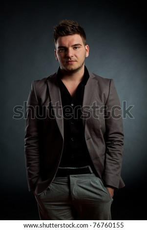 attractive young man wearing elegant suit, over dark background