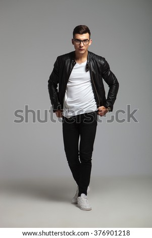 attractive young man wearing glasses walking in studio background while arranging his shirt - stock photo