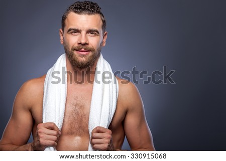 Attractive young man with beard is standing and relaxing after shower. He is holding a white towel on neck and smiling. The man is looking at camera confidently. Isolated and copy space in right side - stock photo