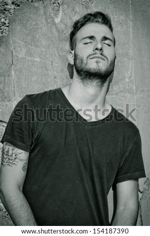 Attractive young man with black t-shirt, against rough wall, with eyes closed - stock photo