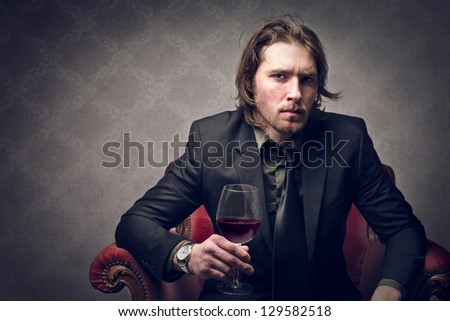attractive young man with glass of red wine - stock photo