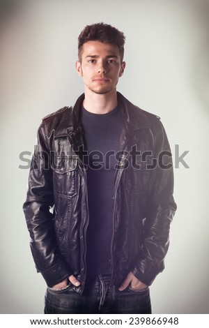 Attractive young man with leather jacket and hands in jeans pockets, looking at camera - stock photo