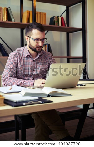 Attractive young man with the glasses looking at his laptop and typing something - stock photo