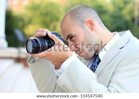 Attractive, Young Mature Professional Photographer Business Man Serious While Taking a Picture - stock photo