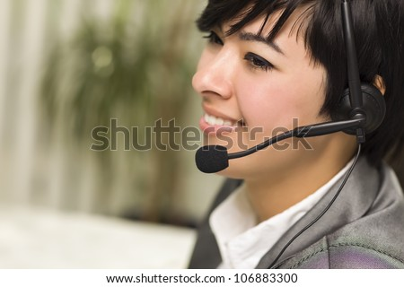 Attractive Young Mixed Race Woman Smiles Wearing Headset in Office Setting. - stock photo