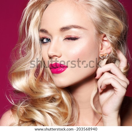 attractive young model with bright make-up and manicure, on pink background - stock photo
