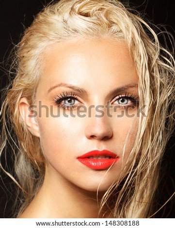 attractive young model with red lips and bright make-up black background, wet hair - stock photo